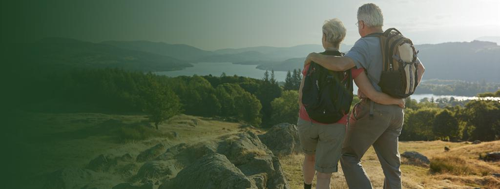 pensions-banner-no-text_V2_1440x540.jpg (Rear View Of Senior Couple Standing At Top Of Hill On Hike Through Countryside In Lake District UK)